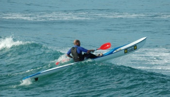 Surf ski riding wave