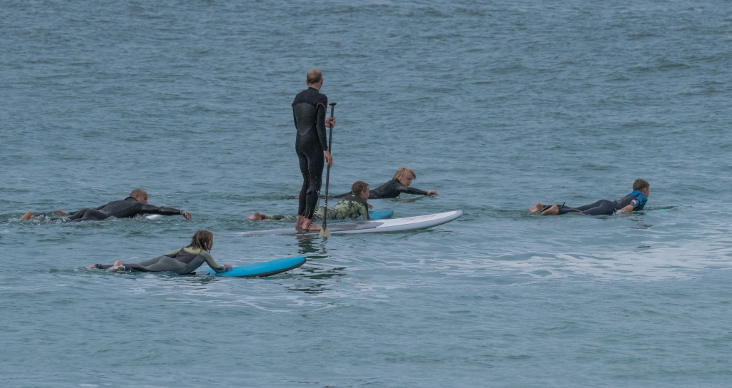 Stand up paddler and surfers at Apollo Bay