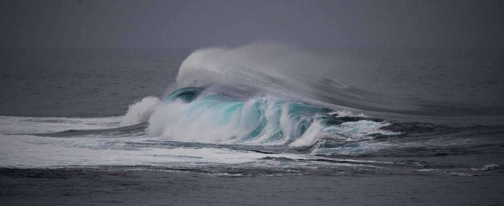 Big breaking swell on Little Henty Reef under stormy skies
