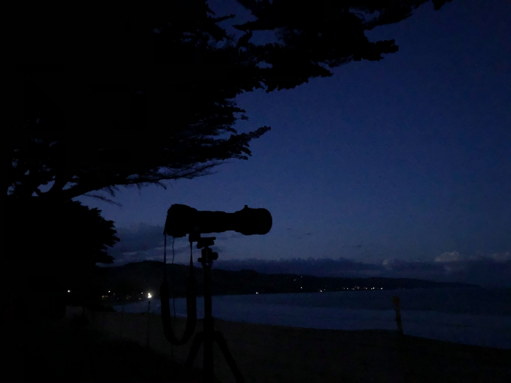 Camera on tripod silhouette at Tuxion after dark