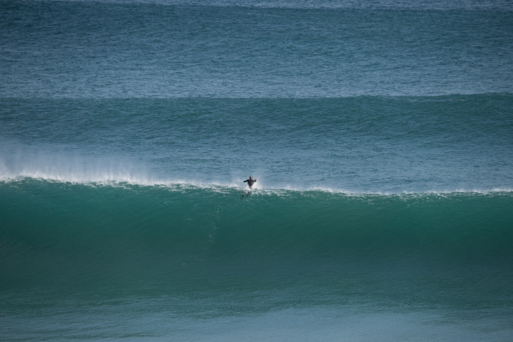 Lone surfer paddling out in big swell at Gibson Steps