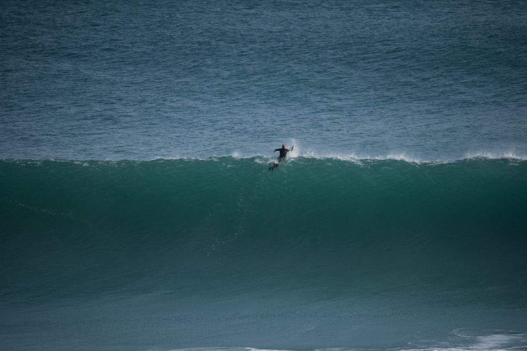 Lone surfer paddling out at Gibson Steps
