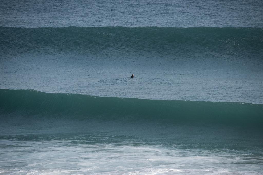 Surfer sitting in trough between large unbroken waves