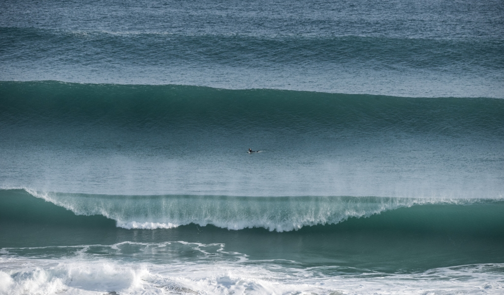 Surfer paddling out in huge surf