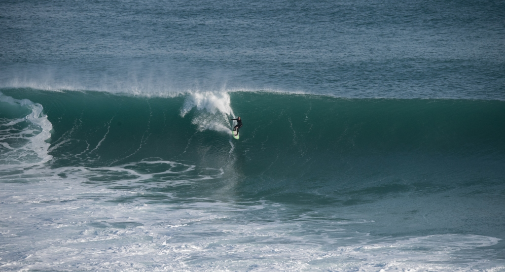 Surfer riding big wave of the day