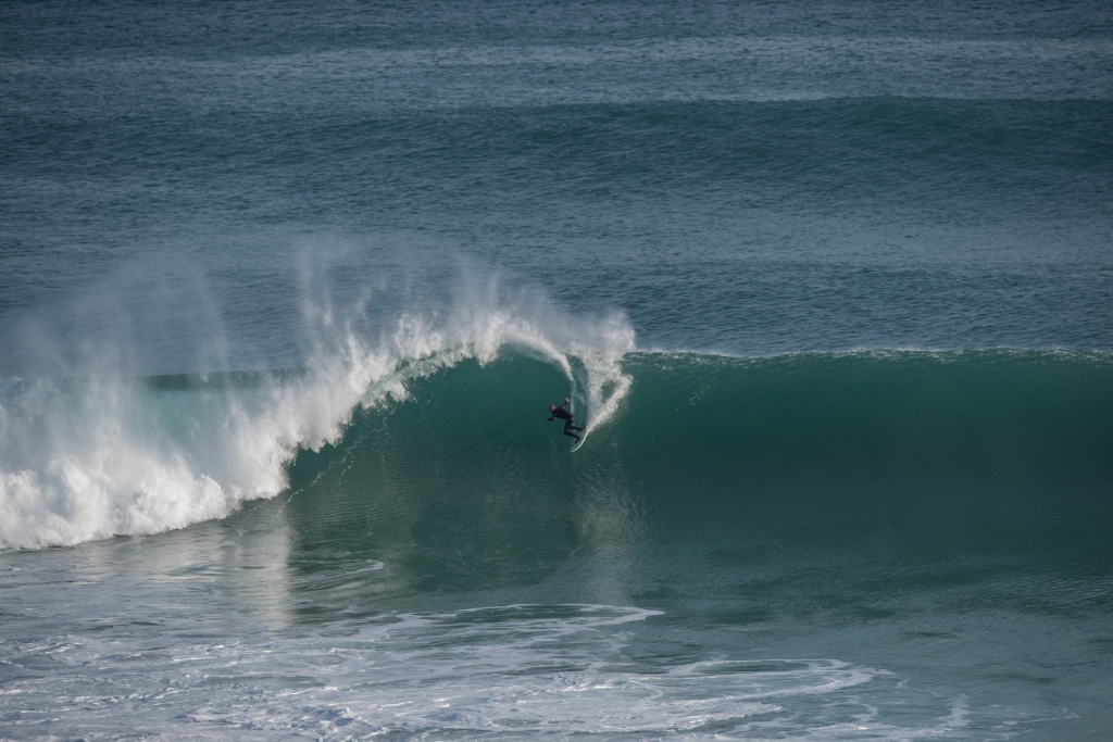 Big sweeping turn by sufrer on huge wave at Gibson Steps
