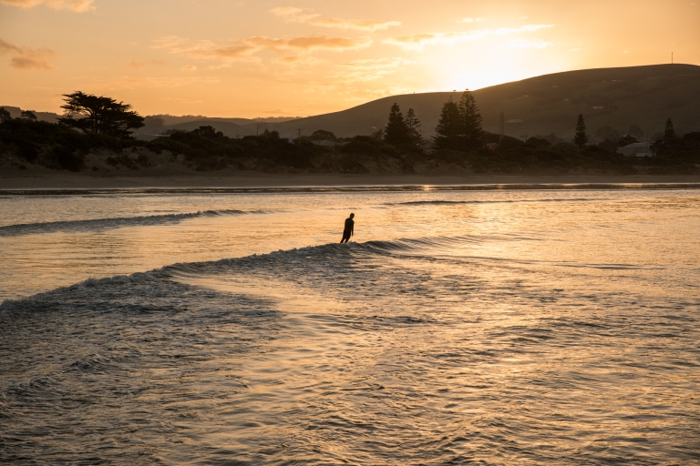 Surf board rider and golden sunset