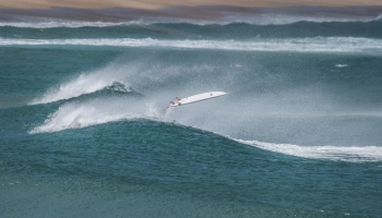Surf board on wave without rider