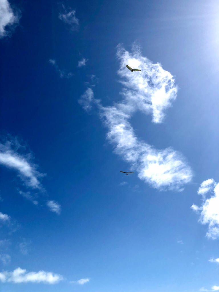 Hang gliders soaring in blue sky with clouds