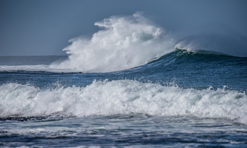 Breaking wave pushing white water high in the air over Little Henty Reef