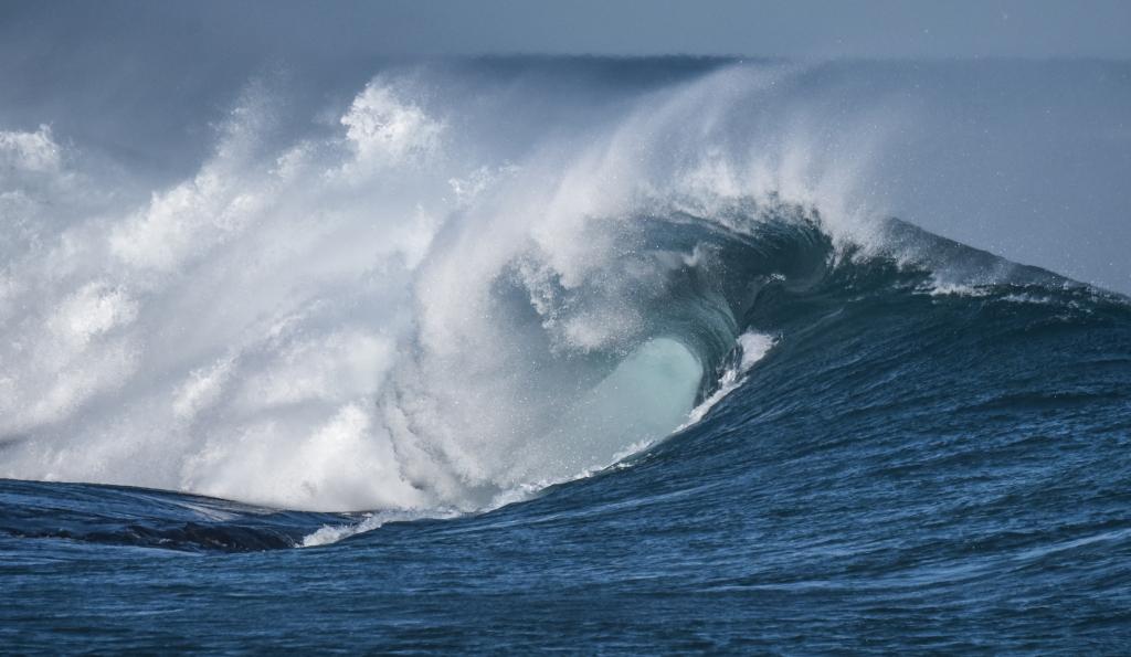 Barrel on wave breaking over exposed reef