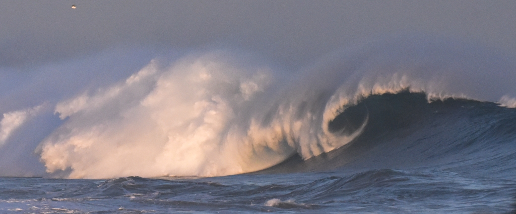 Pastel coloured large breaking wave at sunset