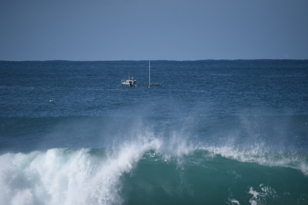 Crayfishing boat partly visible offshore in swell