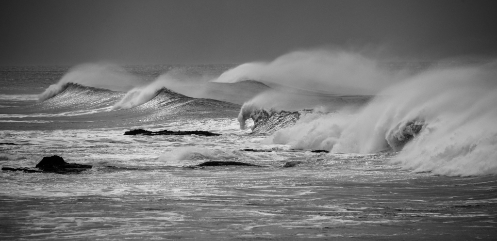 Multiple breaking waves with white spray blown back off them by strong wind