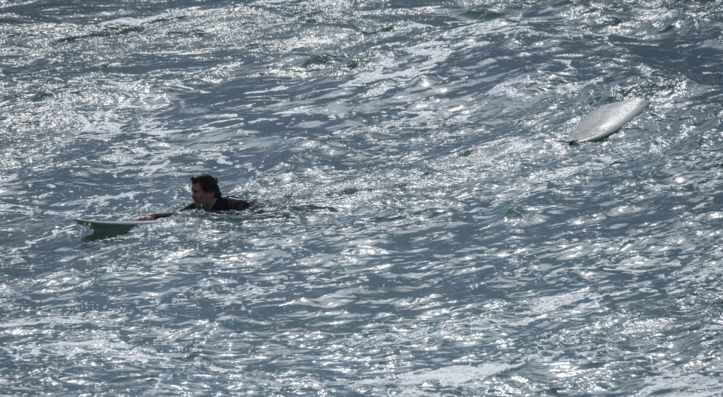 Surfer swimming ashore with board broken in two