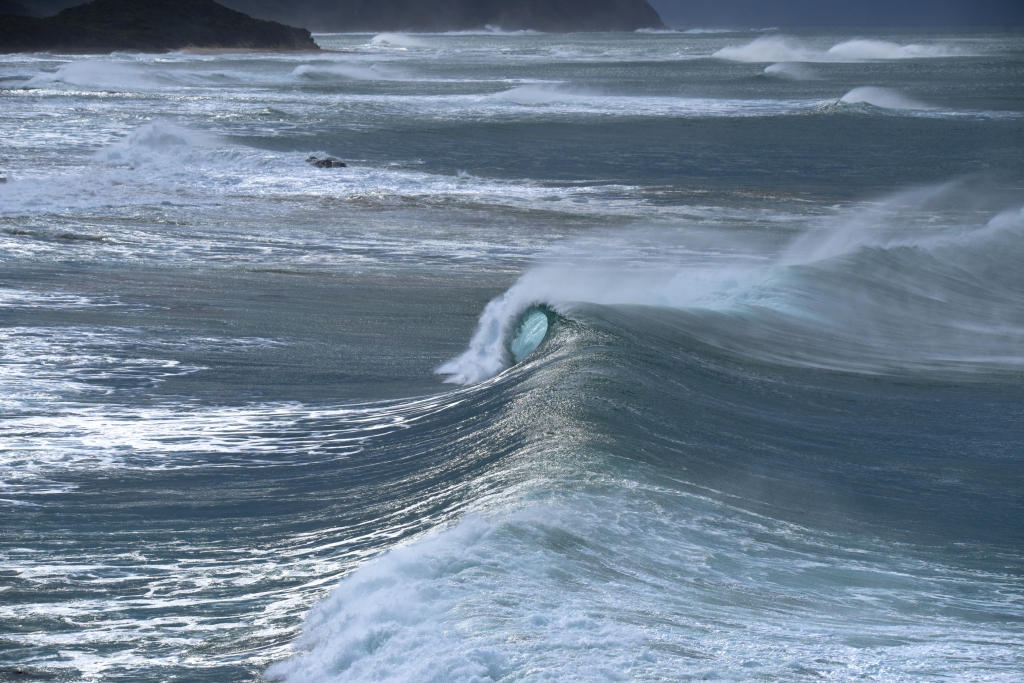Breaking wave in strong winds near shore with aqua barrel visible