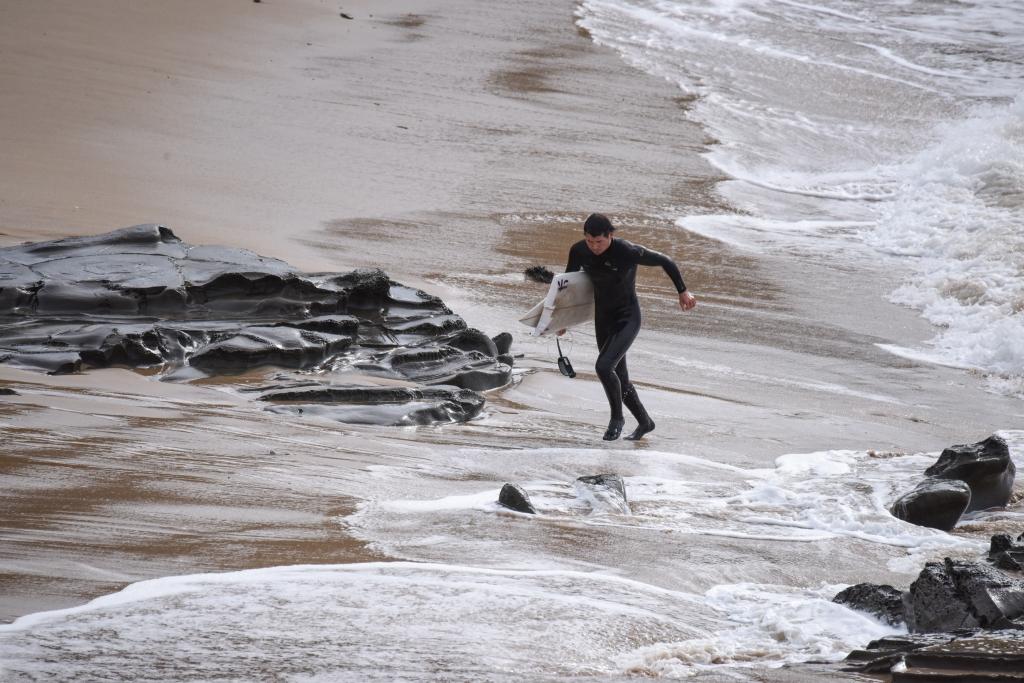 Surfer on shore carrying broken board