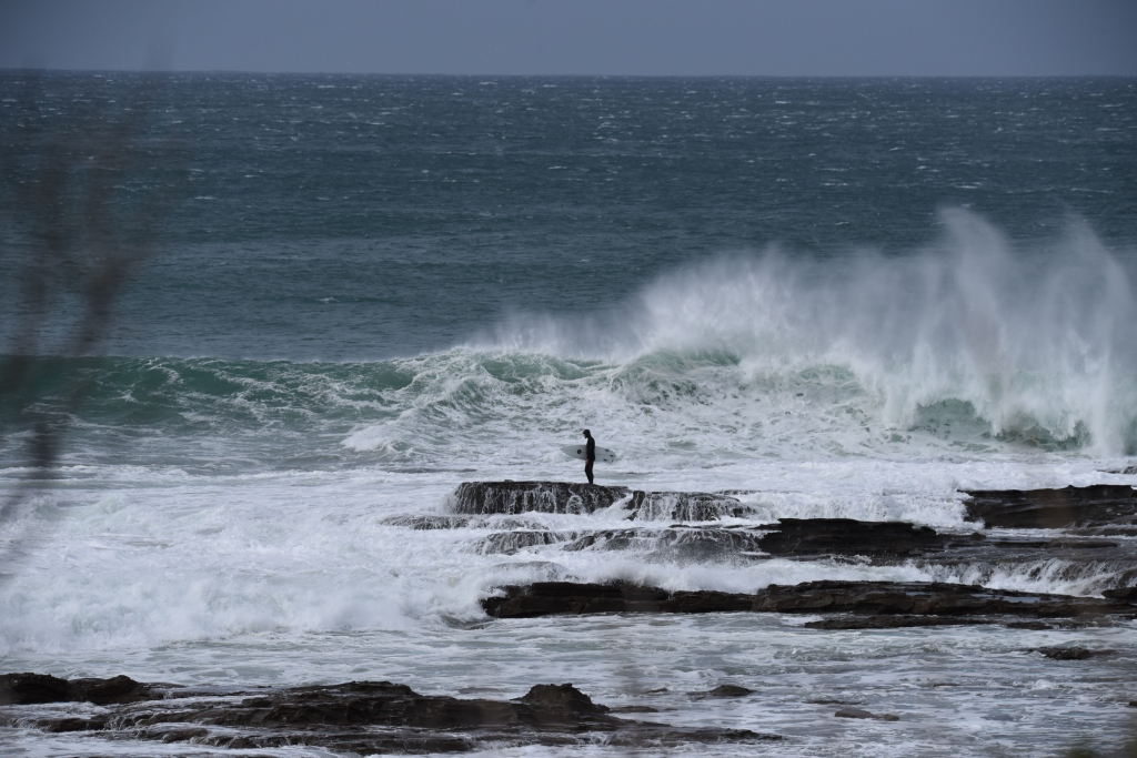 Surfer waiting for right moment to jump off a reef into the surf