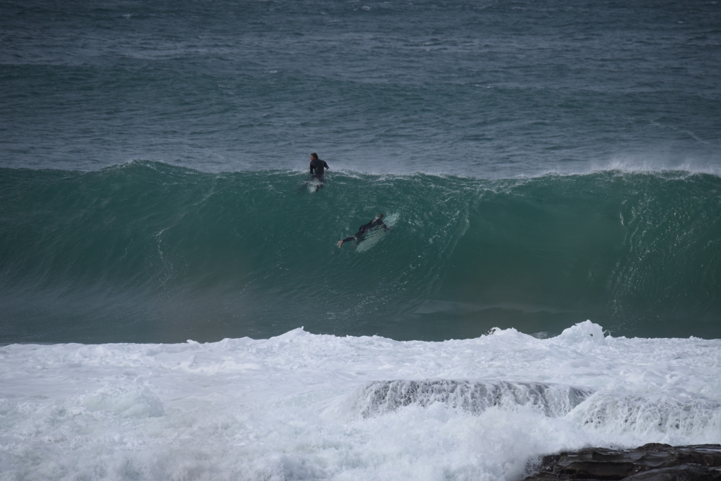 Surfers paddling out over sizeable wave about to break near reef