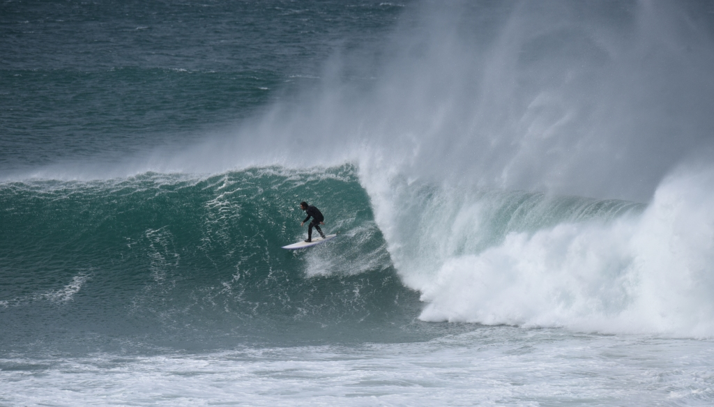 Surfer riding large wave in very strong winds