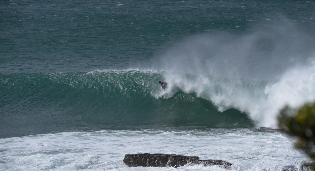 Surfer riding large wave near reef on point