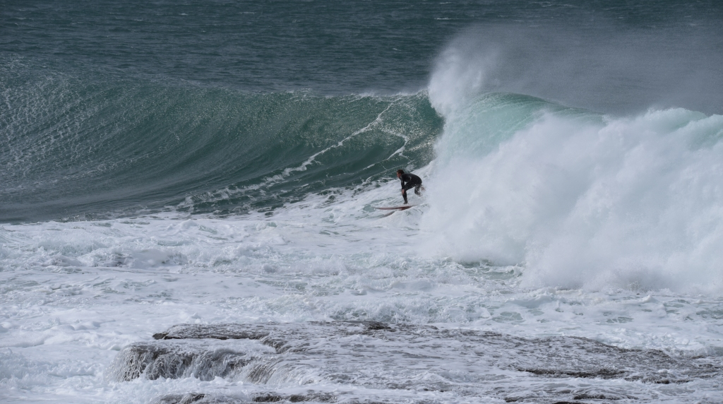 Surfer riding overhead wave near exposed reef