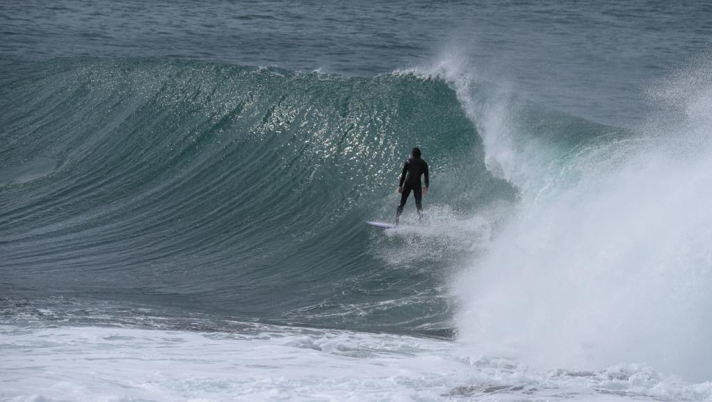 Surfer on clean glassy breaking wave