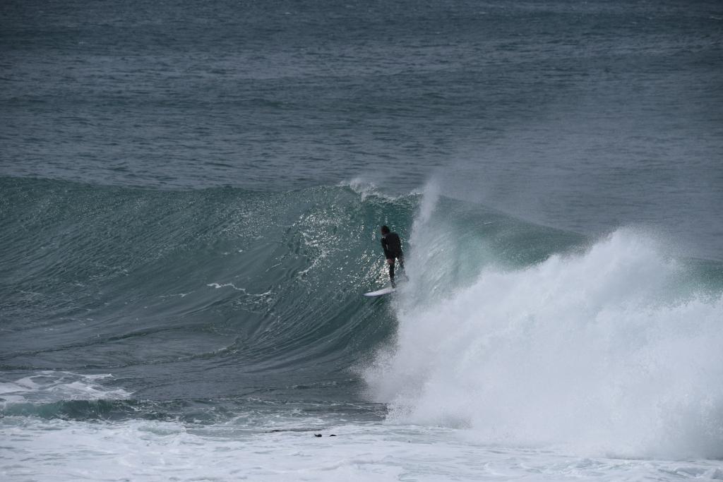 Surfer riding wave near reef below surface