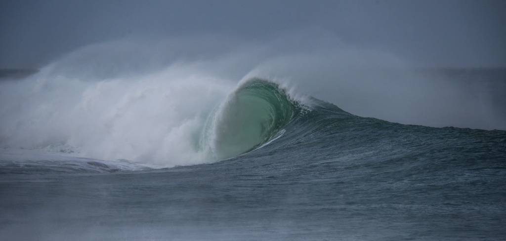 Prominent green barrel on small breaking wave in offshore wind